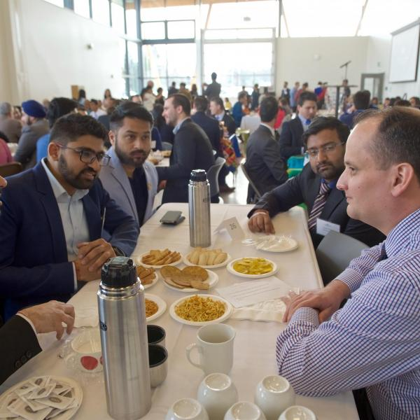MBA internship students sitting at their table with an employer at the 2019 Multicultural Tea