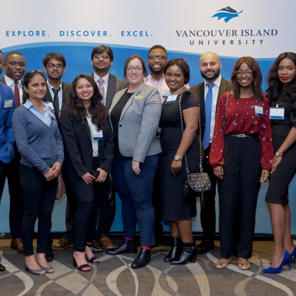 A group of MBA internship students posing for a photo at the 2019 Business Mixer at the Coast Bastion Hotel
