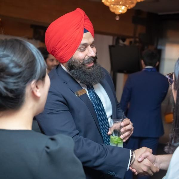 An employer shaking hands with another employer at the 2018 FAB 40 event.