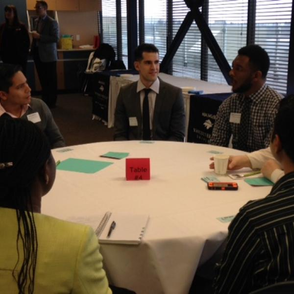 A group of students and employers talking at a table during the LMRT