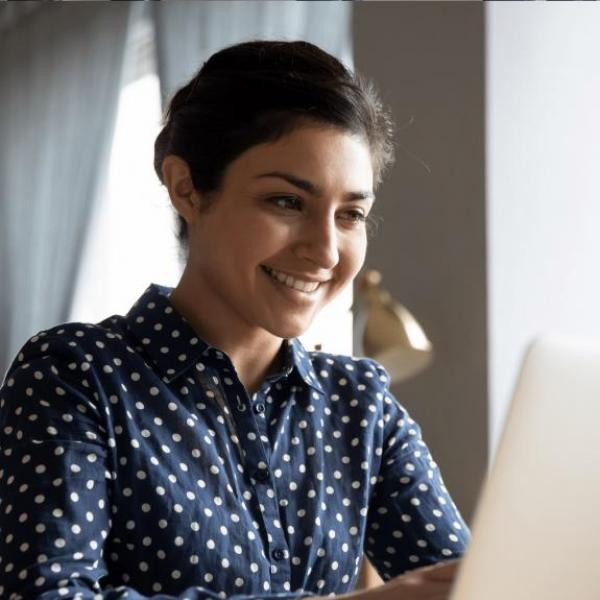 A female student using a laptop and smiling