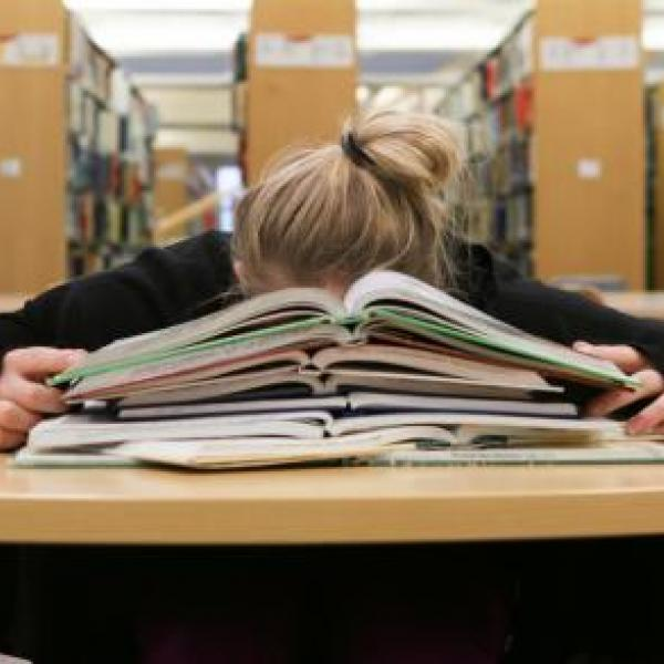 VIU student studying with stack of books