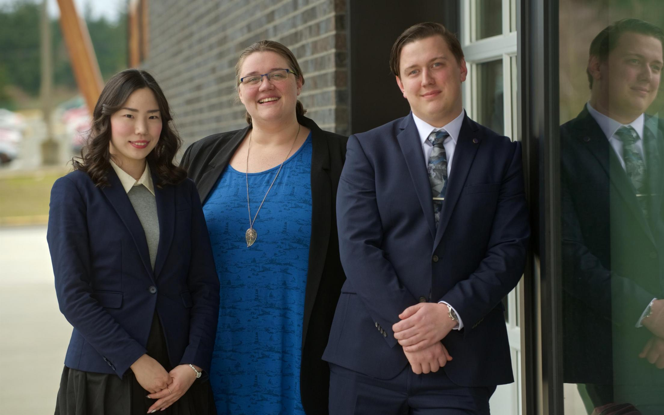 Three MBA internship students posing outside the 2019 Multicultural Tea