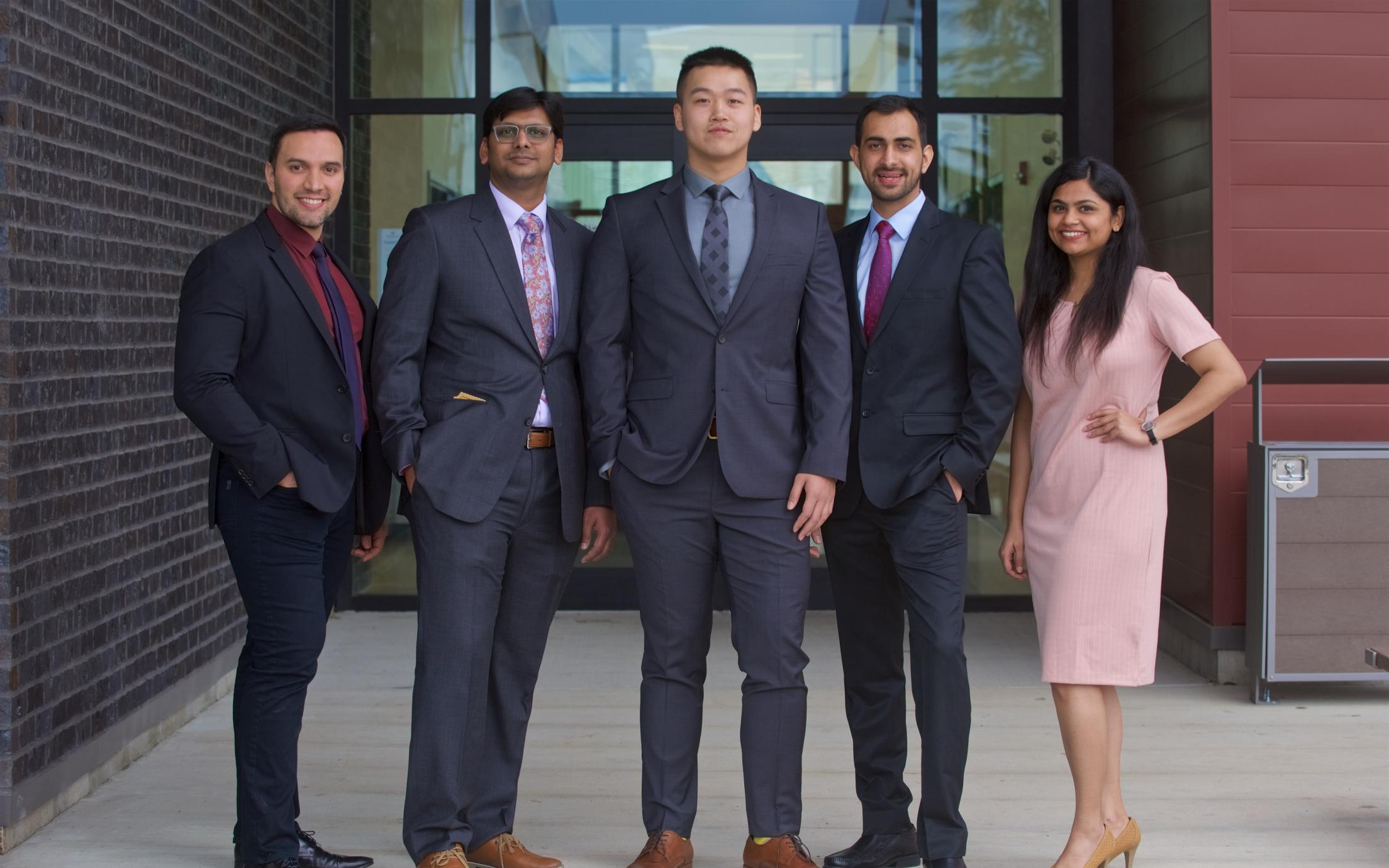 A group of MBA students in business attire poseing for a picture