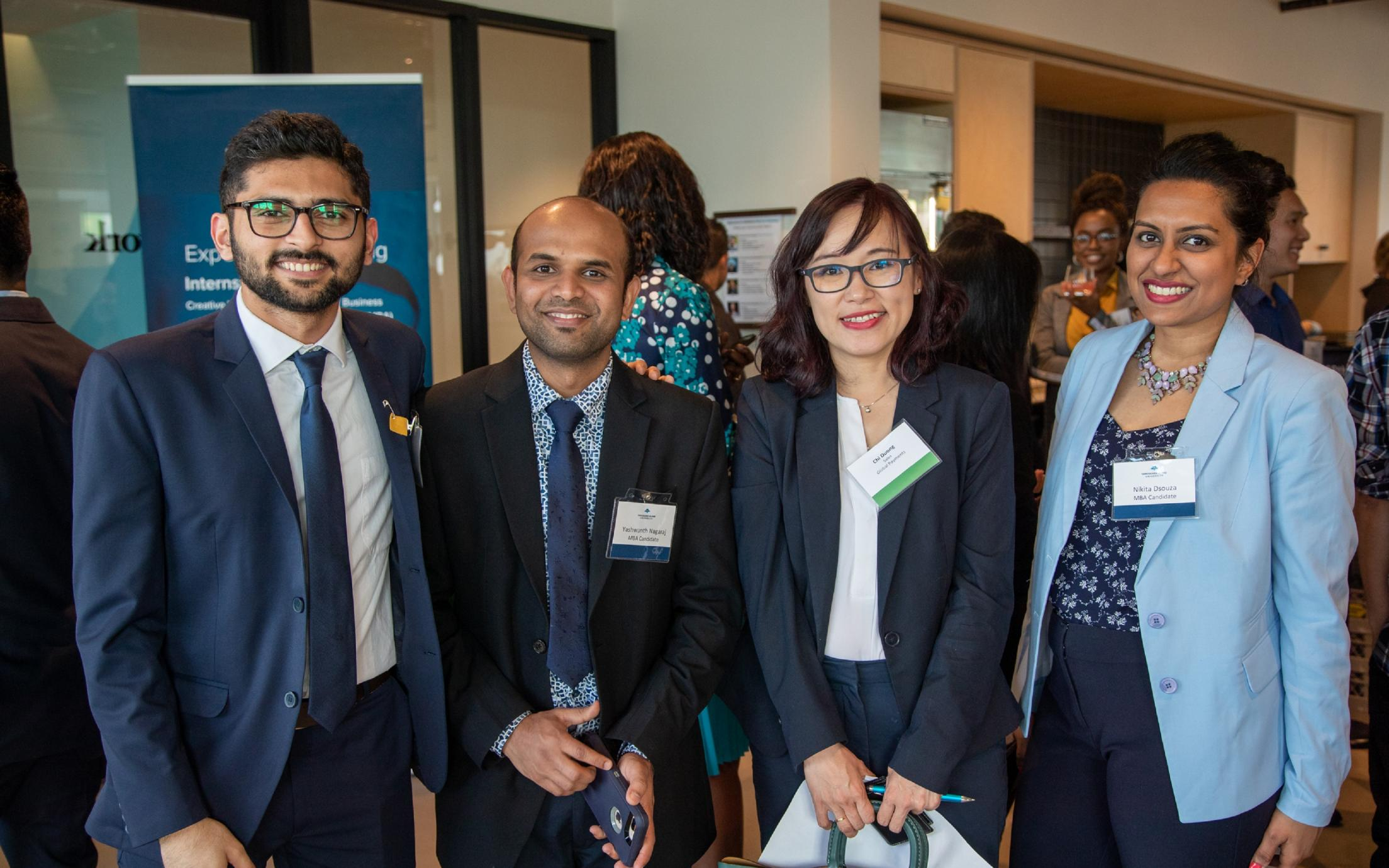 A group of four MBA students standing together at an event