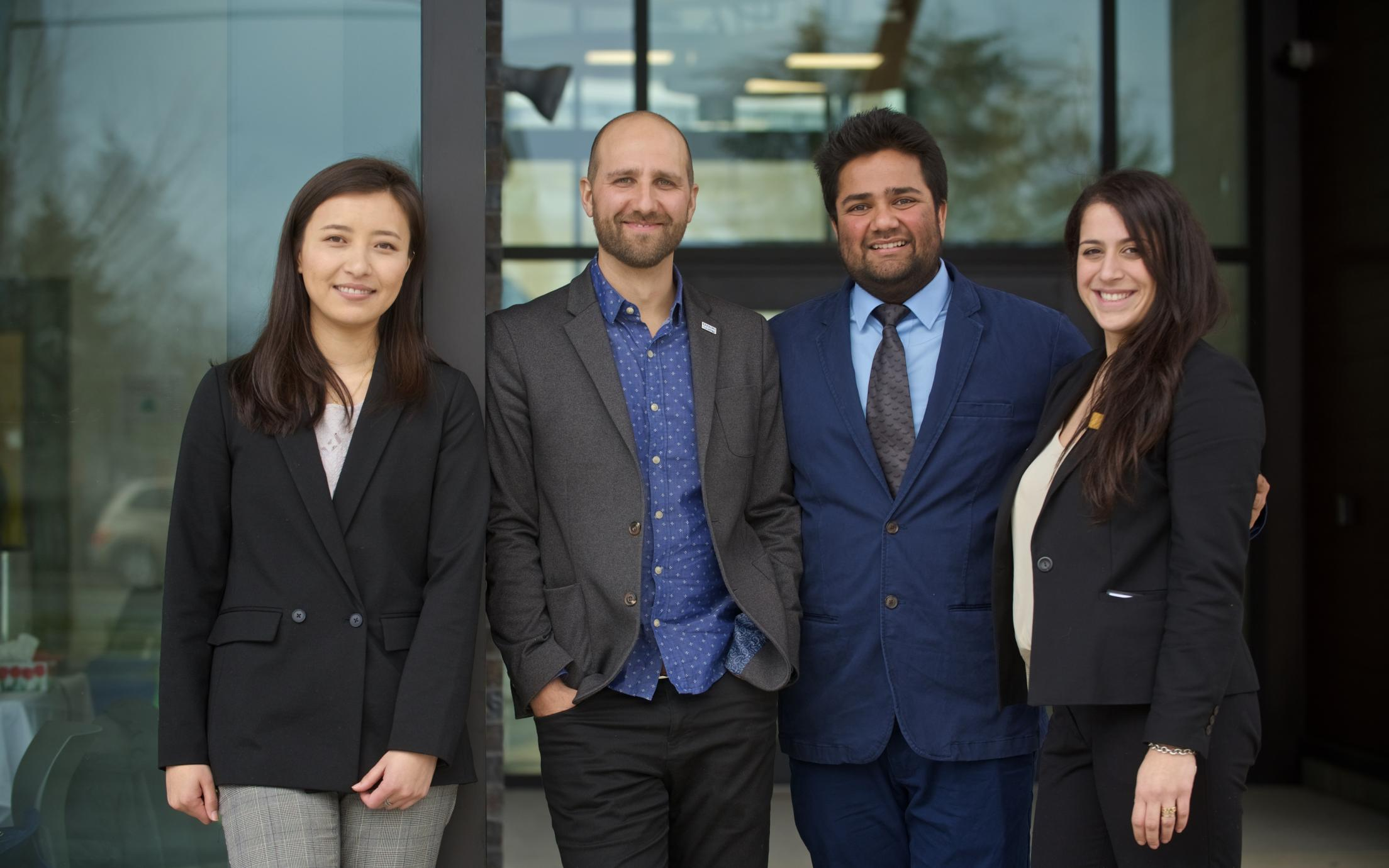 Four MBA students in business attire standing together for a photo