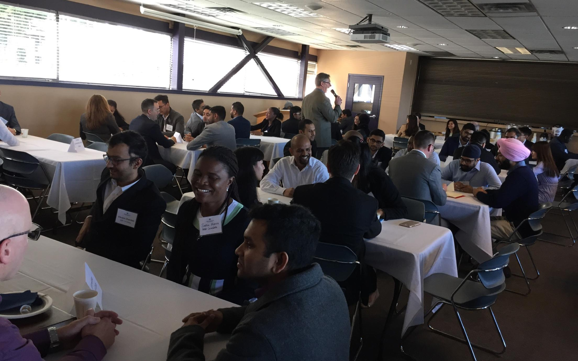 Employers and students sitting at tables during the Labour Market Round Table Event