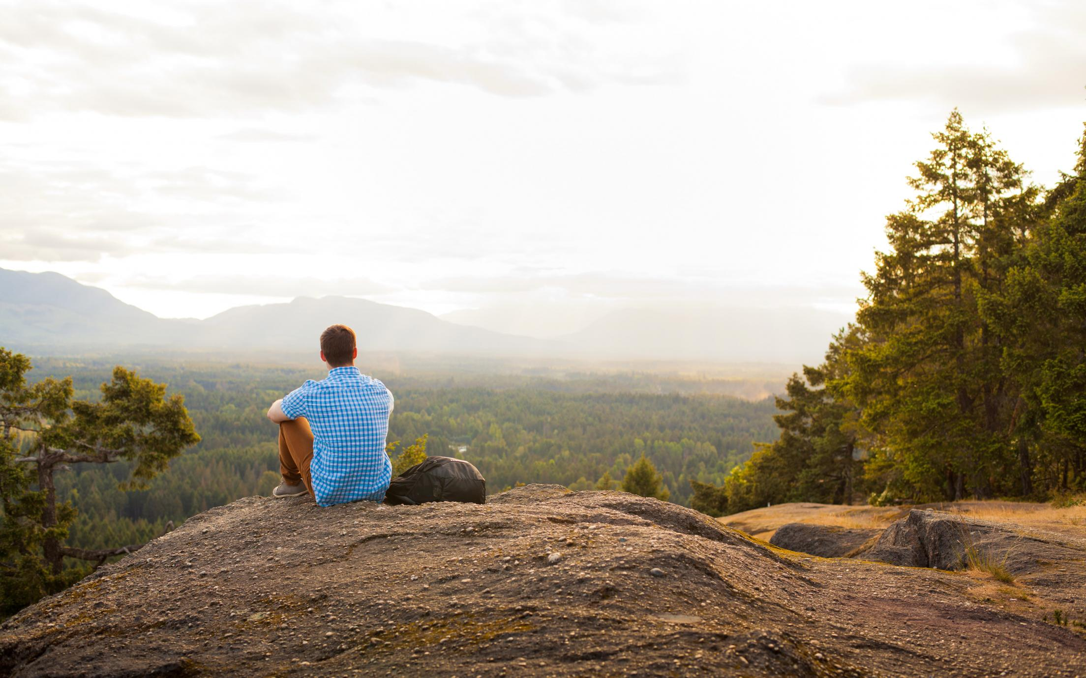 VIU Thrive student sitting on a hilltop