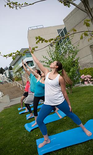 students doing yoga outdoors at VIU Nanaimo campus