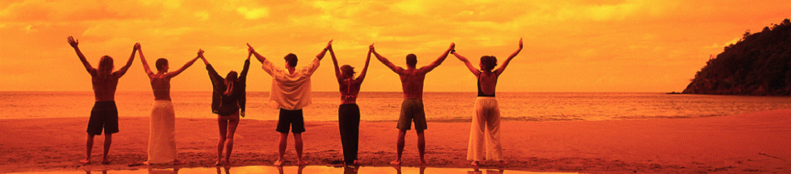 people on beach standing with hands in the air and watching a sunset